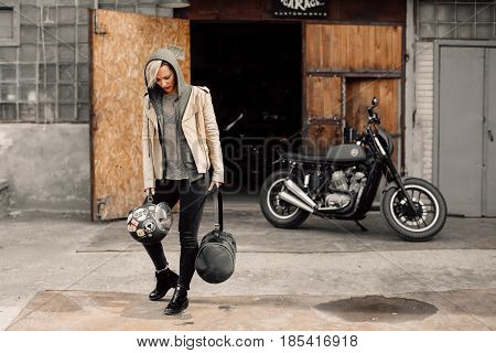 Young woman near a garage. A woman in a leather jacket. Motorcycle near the garage. Motorcycle
