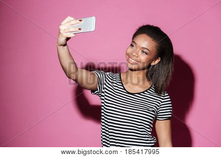 Portrait of a happy young african woman taking selfie and posing isolated over pink background