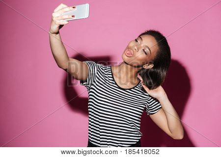 Portrait of a pretty young african woman taking selfie and posing isolated over pink background