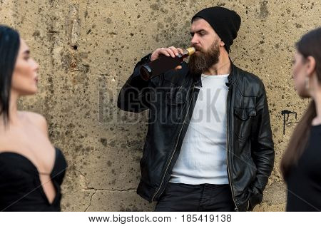 Two sexy women with long hair in black dresses brutal man with beard drinking wine from bottle on blurred grungy cement wall. Unhealthy habits and lifestyle