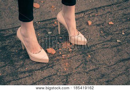 Sexy female legs in fashionable stylish elegant trendy classy beige shoes on high heels on asphalt texture road. Footwear and fashion