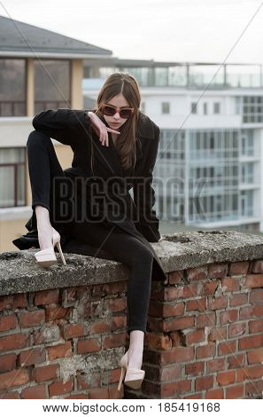 Cute woman in vintage sunglasses fashionable black coat and elegant beige shoes on high heels sitting on red brick fence on urban architecture background. Modern fashion and style