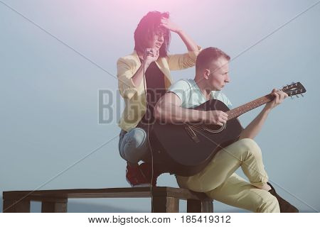 Cute girl or woman singing to microphone and handsome man playing guitar musical instrument on sunny summer day on blue sky. Romantic couple of musicians on table on nature. Music and entertainment