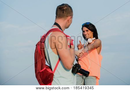 Happy couple of smiling woman or sexy girl in fashion shirt and handsome man or photographer with backpack and camera holding hands on sunny summer day on blue sky. Love and romance