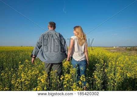 Man With A Young Smiling Woman Are Walking Through A Field