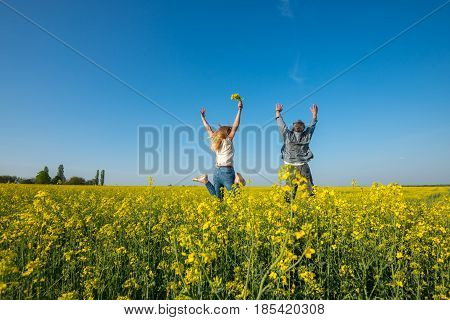 Man With A Young Beautiful Woman Are Jumping And Having Fun In A Field