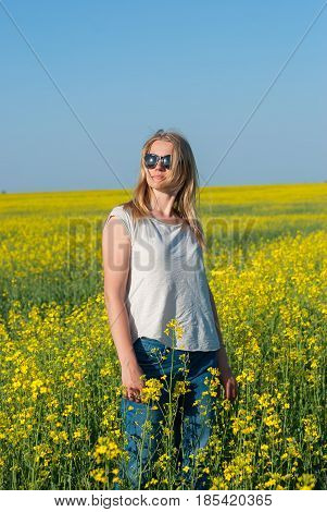 Beautiful Young Woman, Blonde In Sunglasses Poses In A Field Of Yellow Flowers