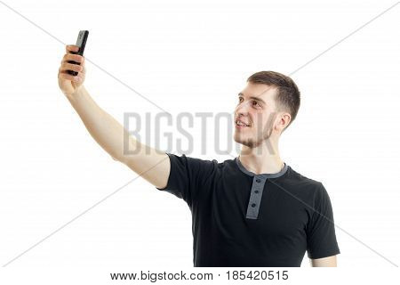 young smiling guy in the black shirt raised his hand up and makes a photo on phone isolated on white background