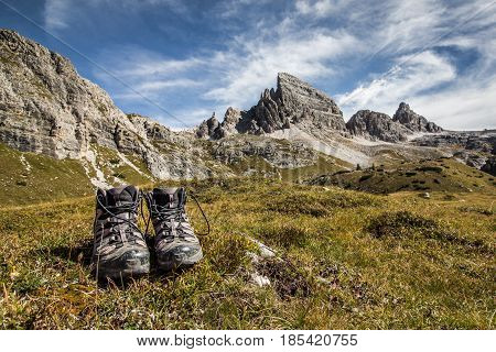 Trekking shoes (boots) on grass in front of stunning mountain scenery and blue skies clear weather. The mountain in the background is Monte Paterno Parco naturale Tre Cime.
