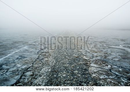 Channel made by an icebreaker on a river with a fog in perspective
