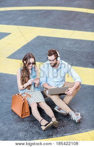 Modern businessman and businesswoman working with laptop and phone sitting on the heliport ground. Lifestyle business concept