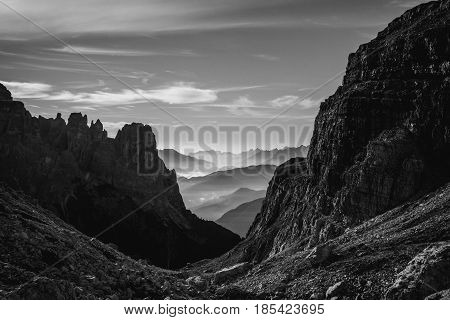 Black and white landscape view of hazy rolling mountains and hills in the Italian Dolomites at sunrise. Landscape orientation