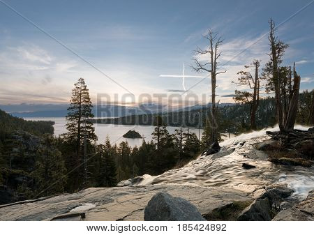 Sunrise at Emerald Bay on Lake Tahoe from the top of Lower Eagle Falls with a cross formed from aircraft trails appears to be a vision.