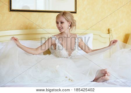 Cheerful Young Bride In Wedding Dress In Hotel Room