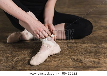 Female dancer ties on her pink ballet slippers with ribbons