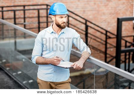 Handsome foreman or builder in helmet supervising a new structure