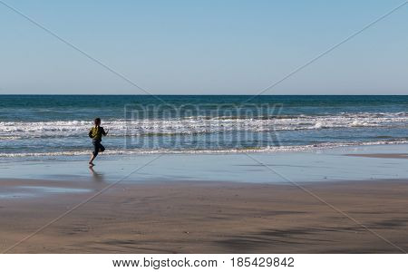 Young Girl Running After Seagull at the Beach