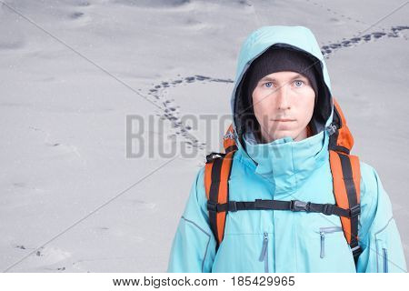 Young man traveler standing on snowy field with footprints in the snow.