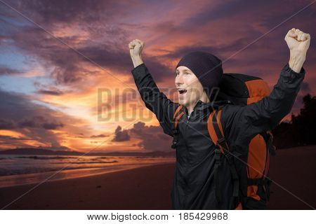 Young man on a background of sea sunset raised her hands up and screams.