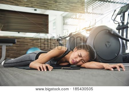 Asian woman fainting while workout at the gym.