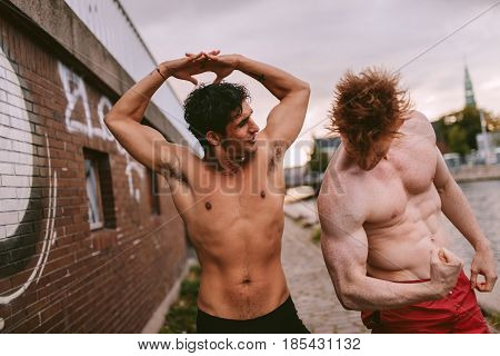 Shot of two young men flexing their muscles outdoors. Muscular young men showing off their body.