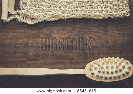 wooden massager brush and bound bast on the brown table