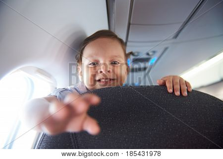 Smiling little boy travel in airlane. Child air plane passenger