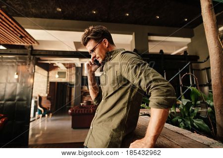 Side view of young man talking on his mobile phone. Creative businessman using mobile phone during office break.