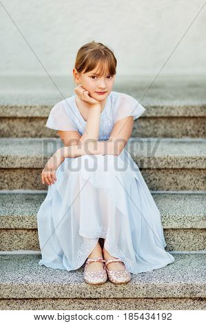 Sweet little preteen girl wearing party dress, sitting on stairs