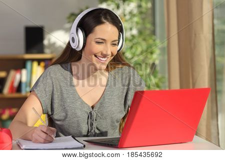 Beautiful portrait of a student learning on line watching video tutorials with a red laptop and headphones in a table at home