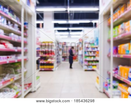 Abstract blurred supermarket aisle with colorful shelves as background