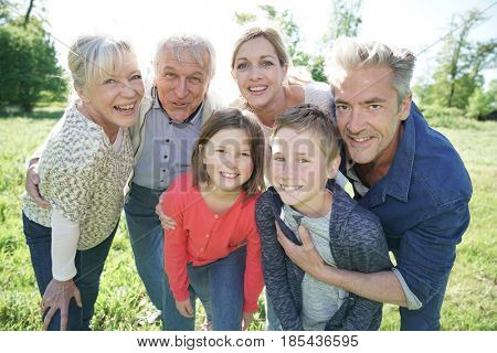 Happy intergenerational family walking in park