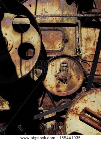 The metal, lines, circles and gears of an old dilapidated farm machinery in Texas form a rusty abstract