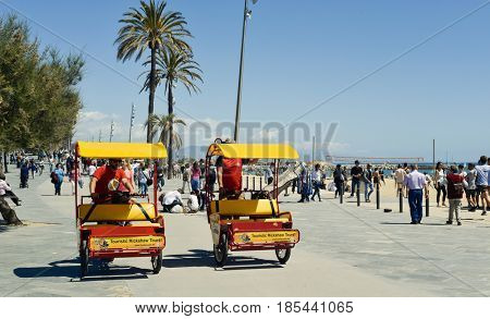 BARCELONA, SPAIN - MAY 7, 2017: A view of the crowded seafront of the Barceloneta Beach in Barcelona, Spain, with a pair of passenger tricycles in the foreground and people walking in the background