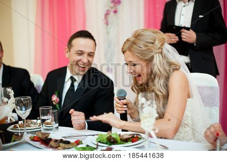 Laughing Bride Looks At Her Wedding Ring Sitting At The Table