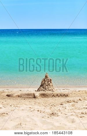 Sand castle and crocodile sculpture on beach summer holiday concept.
