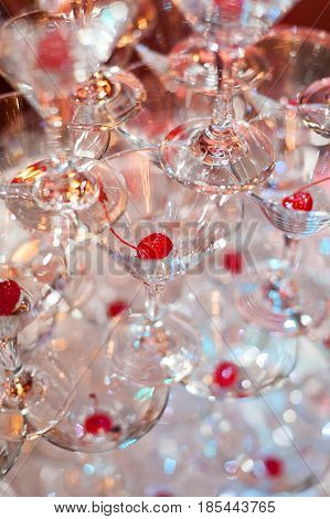 Catering table still life with a pyramid of cocktails glasses close up. Empty wine glasses with red cherry on a table are a tower. Party, fun, alcohol, banquet -concept.
