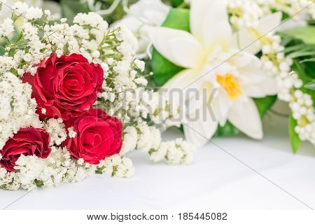 White flowers with red roses decors on white table