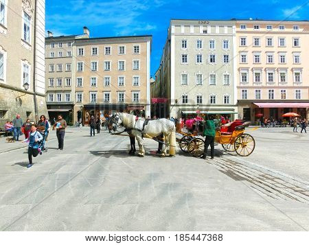 Salzburg, Austria - May 01, 2017: Central place in Salzburg city , Austria with carriages and horses at Salzburg, Austria on May 01, 2017