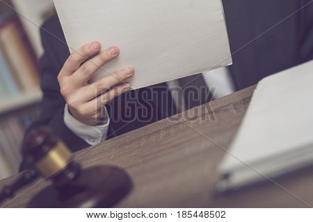 Detail of a judge sitting at his desk holding a file with a new case and studying it. Selective focus