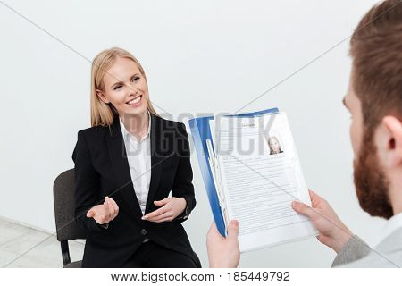 Image of happy lady sitting in office near her boss holding resume over white background isolated. Looking aside.