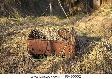The rusty brazier standing in withered grass