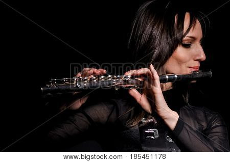 Young elegant woman girl flutist flautist performer playing flute musical instrument on black.