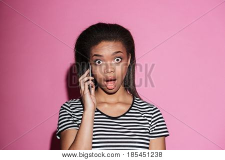 Portrait of a surprised afro american woman gossiping on mobile phone and looking at camera isolated over pink background