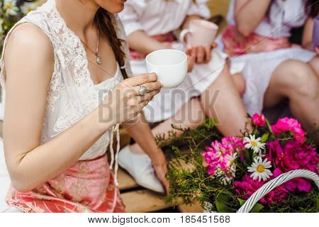 Woman's hands with a cup. Tea or coffee in the cup. Summer day. Home comfort. Woman with a cup in hands. Hold the cup.