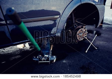 Passenger car is standing on the jack with the unscrewed wheel removed. There is a wrench for the nuts next to it. Concept self-service is repairing the machine by hand in the tanning garage.