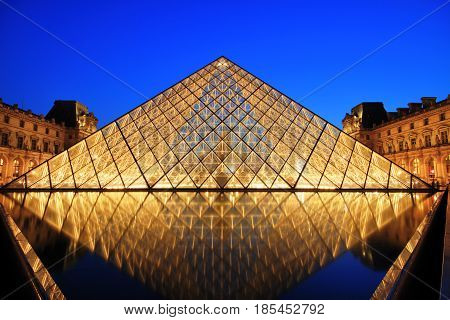 PARIS, FRANCE - JULY 6: The Louvre Pyramid at dusk during the Michelangelo Pistoletto Exhibition on July 6, 2013 in Paris. The Pyramid is the main entrance to the Louvre Museum. Completed in 1989 and became one of the landmarks of Paris
