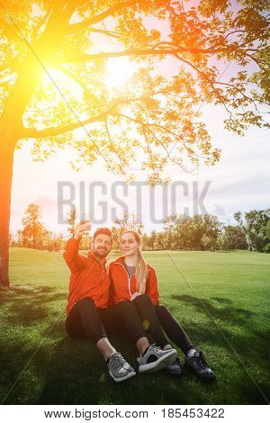Sporty couple making selfies in green park or forest. Man and woman sitting on green grass and posing for photo camera. Toned.