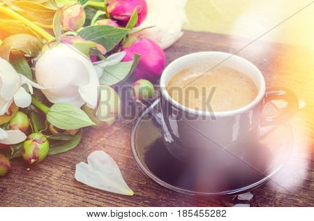 Espresso and flowers peony background. A cup of coffee and Peonies on a rustic wooden table. Breakfast on Mothers day Valentines Day or Womens day. Spring or summer morning concept.