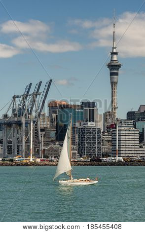 Auckland New Zealand - March 3 2017: Portrait of container terminal with its cranes under blue sky and behind greenish ocean water. City skyline with office towers as background. White sailing boat on the water.